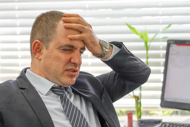 Лицо расстроенного офисного работника, менеджера человека в стрессе перед монитором компьютера