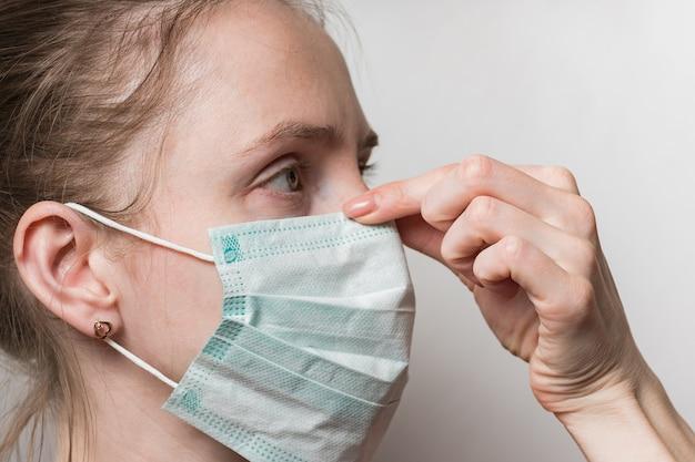 医療マスクの女性の顔。女の子は鼻に防護マスクを押します。インフルエンザウイルスの保護
