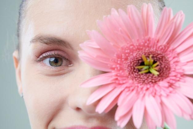 ピンクの花を持つ女性の顔