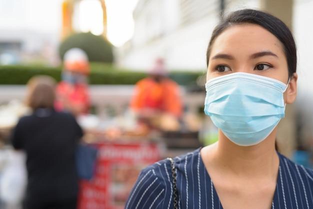 Лицо молодой азиатской бизнес-леди с маской для защиты от вспышки коронавируса думает в городе
