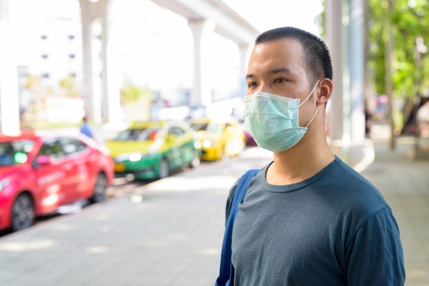 市内のタクシー乗り場でのコロナウイルスの発生からの保護のためのマスクを持つ若いアジア人の顔