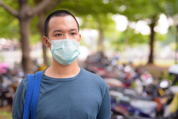 屋外の都市でのコロナウイルスの発生からの保護のためのマスクを持つ若いアジア人の顔