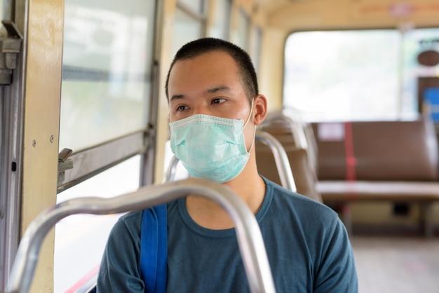 Лицо молодого азиатского человека с маской, едущего на автобусе с расстояния