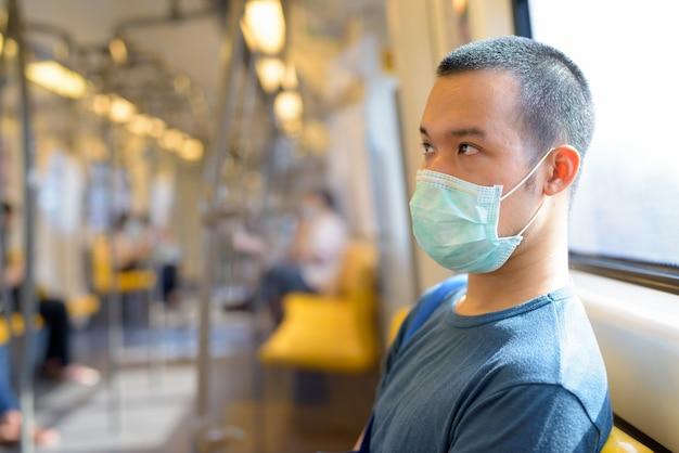 電車の中の距離で座っているマスクを持つ若いアジア男の顔