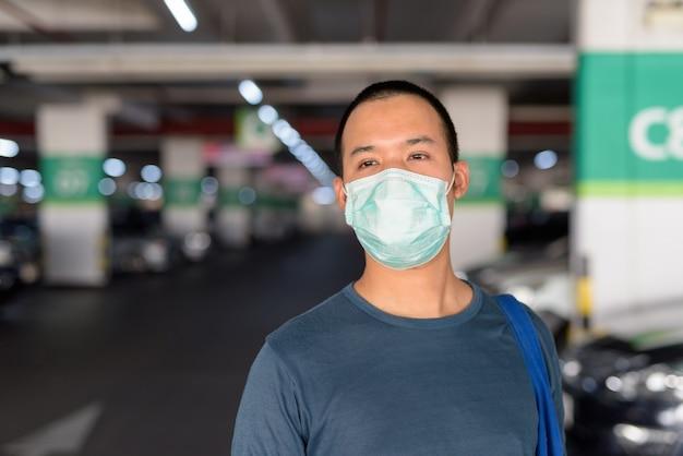 Лицо молодого азиатского человека с маской, думая на стоянке