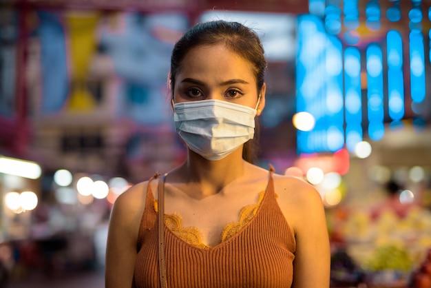 チャイナタウンで夜のコロナウイルスの発生からの保護のためのマスクを身に着けている若いアジア観光客女性の顔