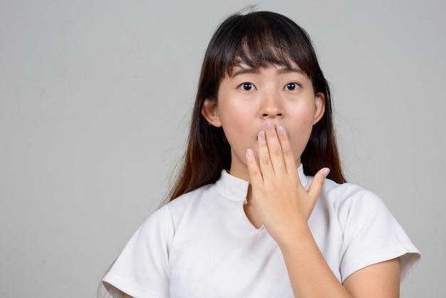 口を覆い、ショックを受けている若いアジアの女性の顔
