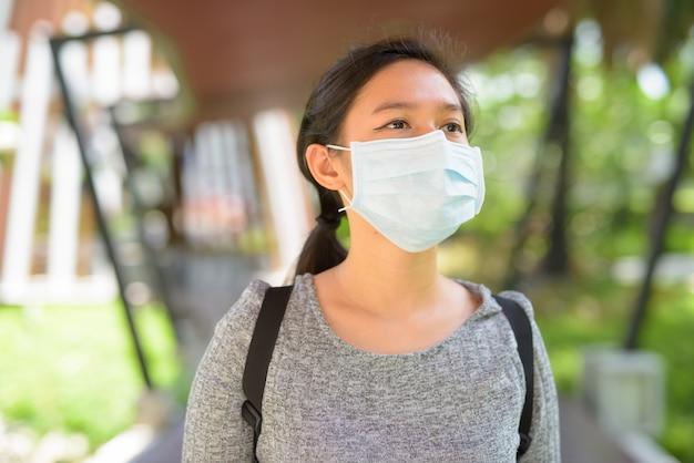 マスクを着用し、屋外で考える若いアジアの女性の顔