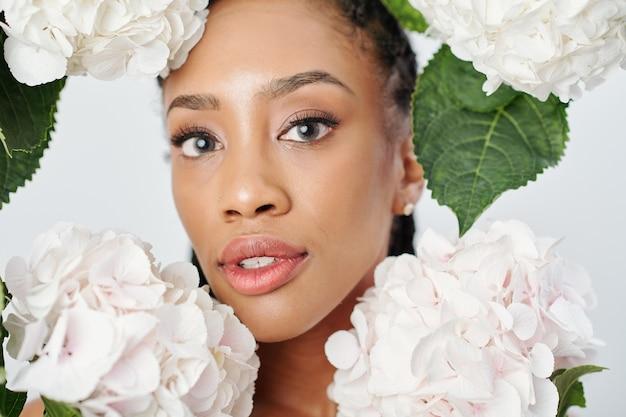 흰색 수국 꽃 가운데 젊은 매력적인 아프리카 계 미국인 여자의 얼굴