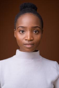 茶色の背景に若い美しいアフリカの女性の顔