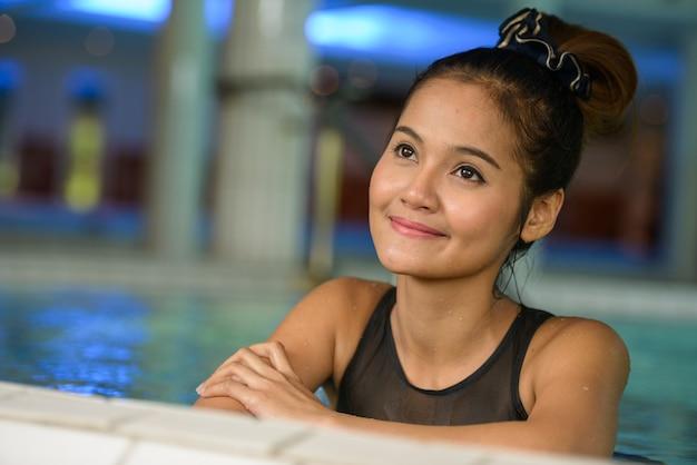 スパで考えてリラックスして若い美しいアジアの観光客の女性の顔