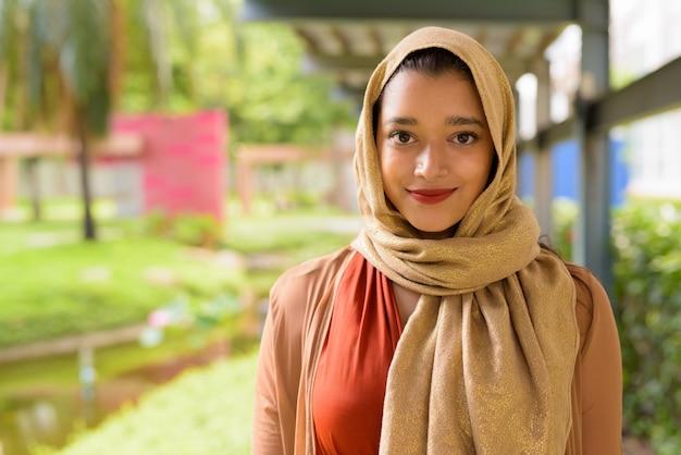 Лицо молодой красивой индийской мусульманской женщины в парке на открытом воздухе