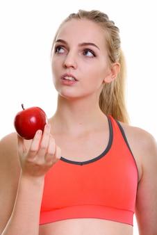 赤いリンゴを保持している若い美しい10代の少女の顔