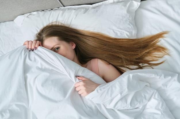 담요와 침대에서 베개에 누워 젊은 아름 다운 여자의 얼굴, 그녀의 얼굴을 덮고 웃는 소녀 포즈, 상위 뷰