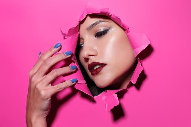밝은 메이크업과 붉은 입술을 가진 젊은 아름 다운 여자의 얼굴은 분홍색 종이에 구멍을 통해 보인다.