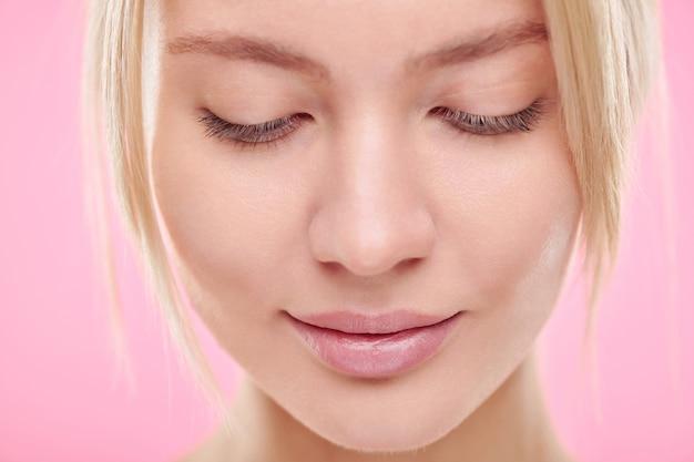 ピンクの壁を見下ろす自然なメイクと若い金髪の穏やかな女性の顔