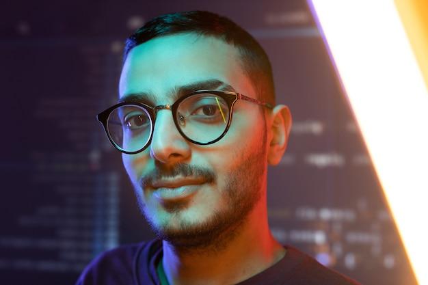 データのある大画面に立ち向かう眼鏡の若い賢い自信のあるプログラマーまたはソフトウェア開発者の顔