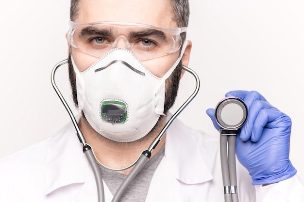 Covid19で病気の患者を診察しながら聴診器を保持しているホワイトコート、呼吸器、手袋、眼鏡の若い臨床医の顔
