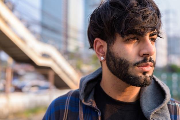 屋外の街の通りで考えている若いハンサムなひげを生やしたインドの流行に敏感な男の顔
