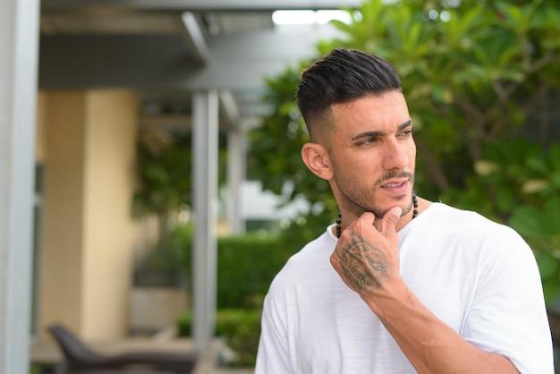 屋外で自然と考えている若いハンサムなひげを生やしたペルシャ人の顔