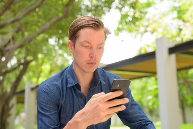 屋外の公園で電話を使用して若いハンサムなブロンド実業家の顔