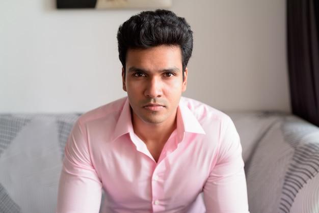 家にいるリビングルームで若いハンサムなインドのビジネスマンの顔