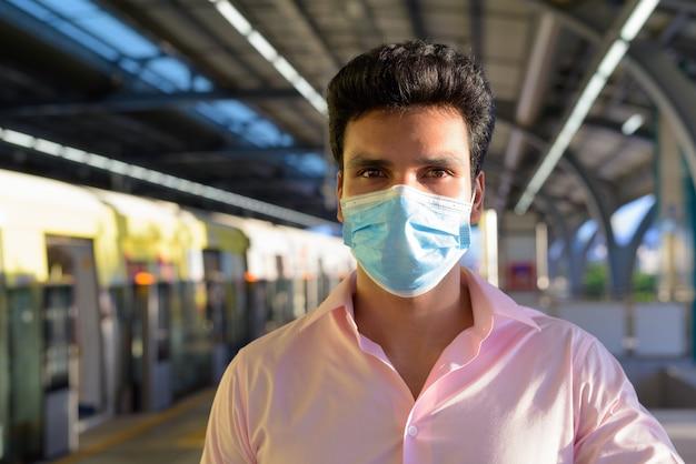 スカイトレインの駅でマスクと社会的距離を着ている若いインドのビジネスマンの顔
