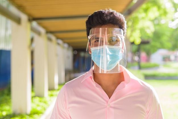 Лицо молодого индийского бизнесмена с маской и щитком для лица в парке на открытом воздухе