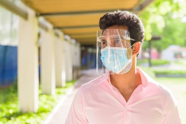 屋外の公園で考えているマスクとフェイスシールドを持つ若いインド人実業家の顔