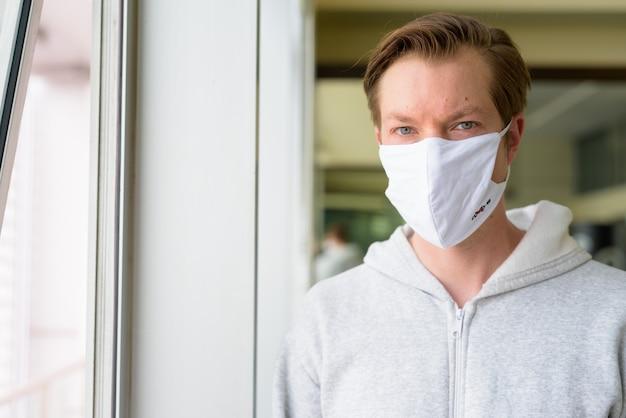 ジムの準備ができて窓際のマスクを持つ若い男の顔