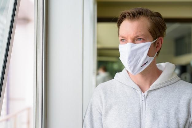 マスクを考えて、ジムの準備ができて窓の外を見ている若い男の顔