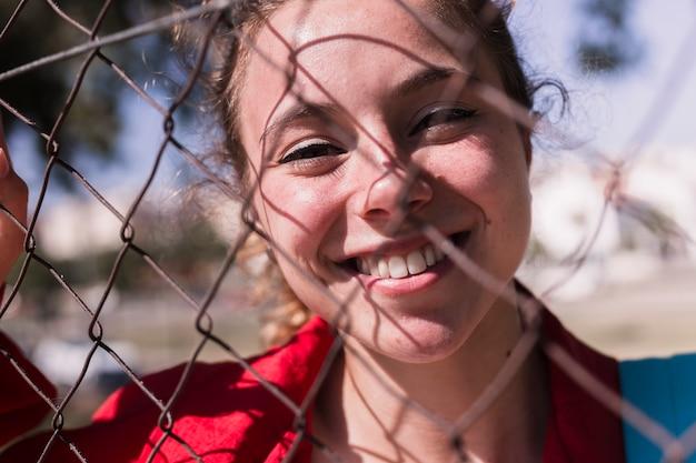 Лицо молодой улыбающейся девушки, стоящей за решеткой