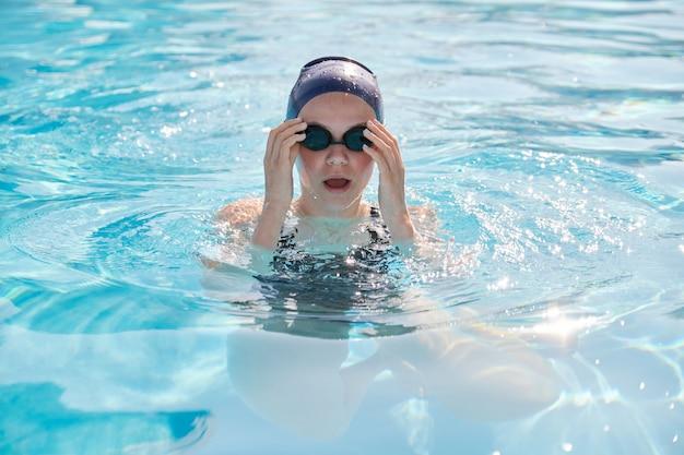 プールで若い女性水泳選手、水泳用キャップゴーグルの女の子の顔