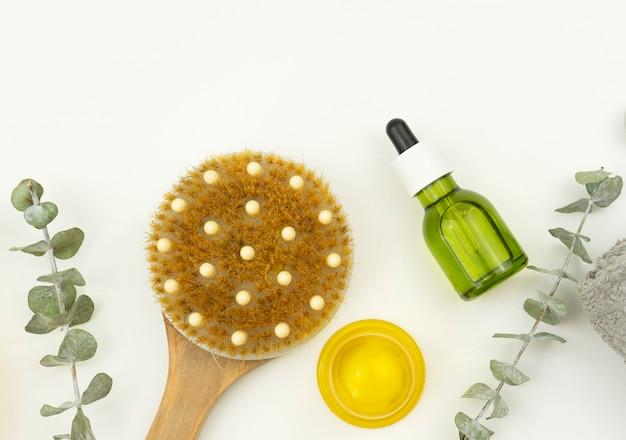 Масло и валик для лица, кисть для сухого массажа и хлопковое полотенце лежат на белом столе.