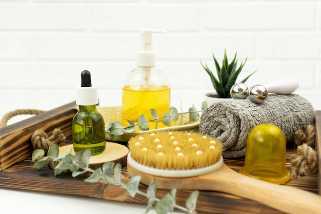Масло и валик для лица, кисть для сухого массажа и хлопковое полотенце лежат на деревянном подносе.