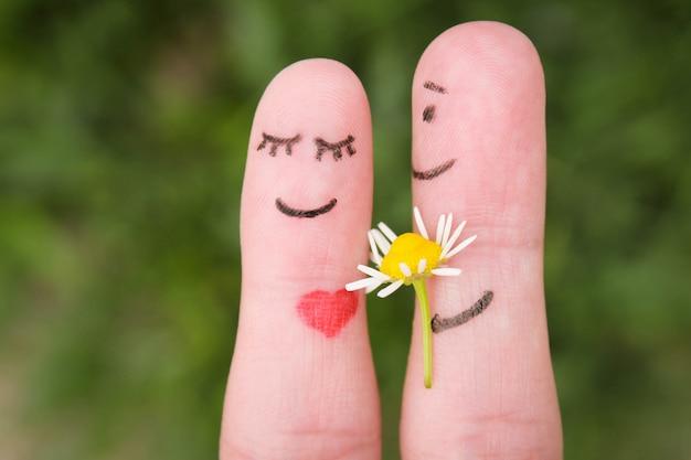 指で顔を描いた。男性は女性に花をあげています。