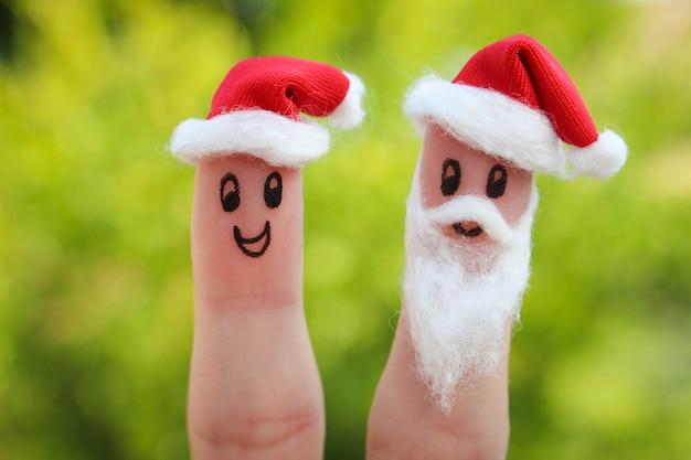 Лицо нарисовано на пальцах. дед мороз дарит подарки