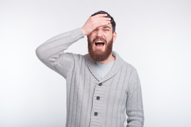 Face palm gesture is made by a young bearded man on white .