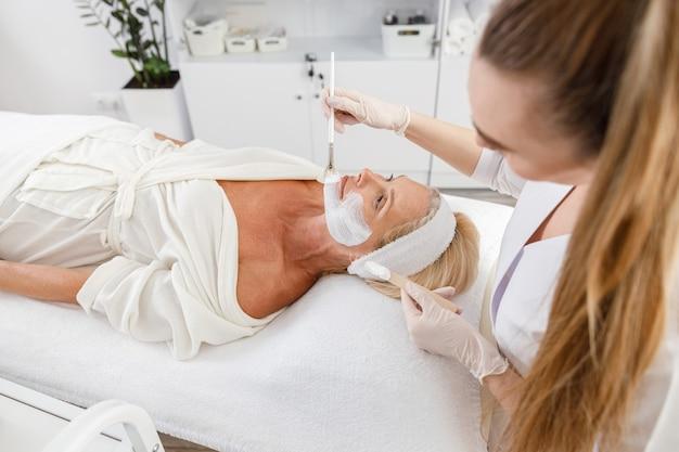 Маска-пилинг для лица, спа-косметические процедуры, уход за кожей. старшая женщина, получающая уход за лицом косметологом в спа-салоне.