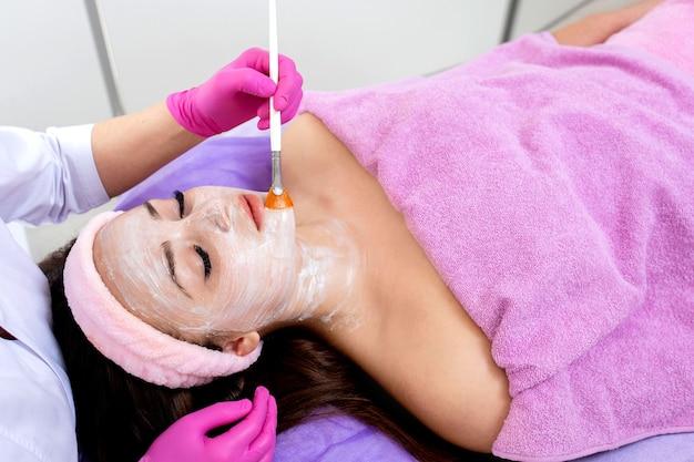 Маска-пилинг для лица, спа-косметические процедуры, уход за кожей. женщина получает уход за лицом косметолог в спа-салоне, вид сбоку, крупный план. антивозрастной уход. косметология и профессиональный уход за кожей лица.
