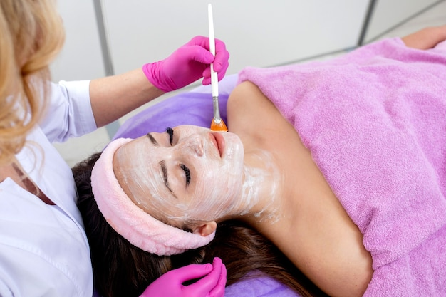 Face peeling mask, spa beauty treatment, skincare. woman getting facial care by beautician at spa salon, side view, close-up. anti-aging treatment. cosmetology and professional facial skin care.