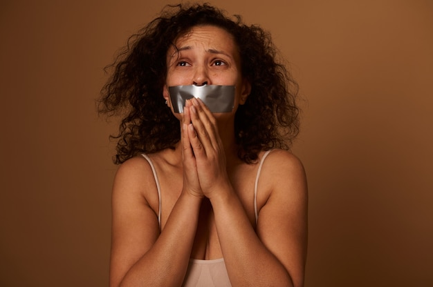 Face portrait of a frightened desperate mixed race hispanic woman with sealed mouth looks up with a plea for help. social concept of international day for elimination violence against women