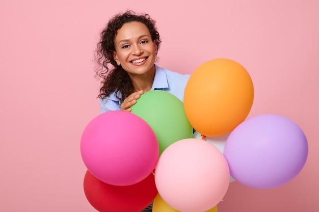 コピースペースとピンクの明るい背景の上に分離されたカラフルな気球の後ろに立っている歯を見せる笑顔で笑っている美しい見事なアフリカ系アメリカ人の巻き毛の髪の女性の顔の肖像画