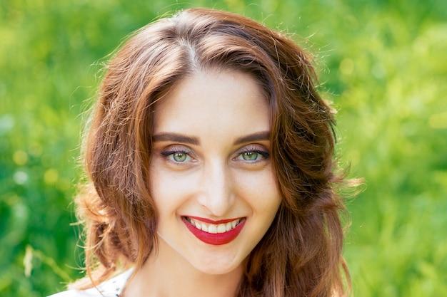 Лицо портрет молодой улыбающейся женщины, внешней летом.