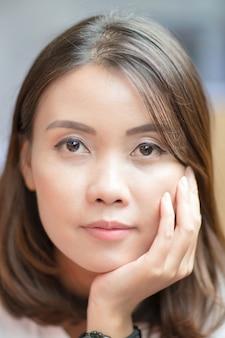 Face portrait of young asian woman touching her cheek
