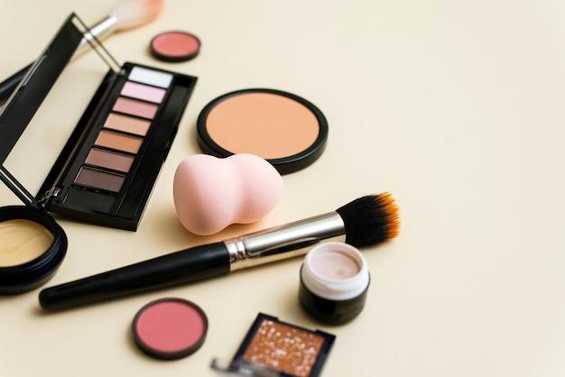 ベージュの背景にフェイスパウダー、ブラシ、さまざまな化粧品の装飾用メイクアップ製品