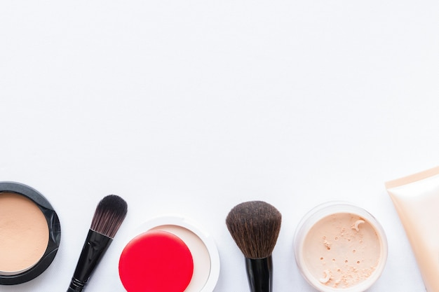 Face powder and brush for makeup on white background