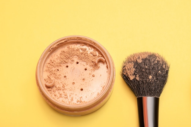 Face powder and brush on yellow background