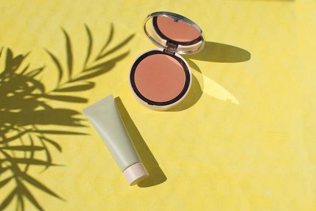 Face powder foundation blush make up flat lay yellow background