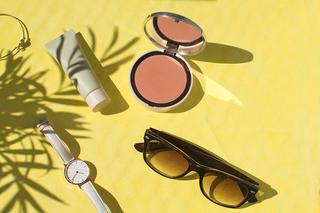 Face powder foundation blush watch sunglasses bracelet flat lay
